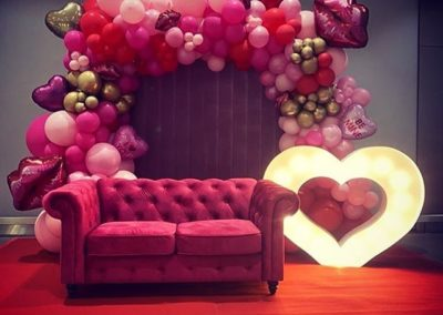 Light up love heart shape sign with red and pink balloons surrounding it next to a pink lounge for a photo opportunity for valentines day